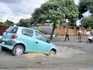 Car stuck in sink holes and liquefaction on roads - North New Brighton in Christchurch, New Zealand